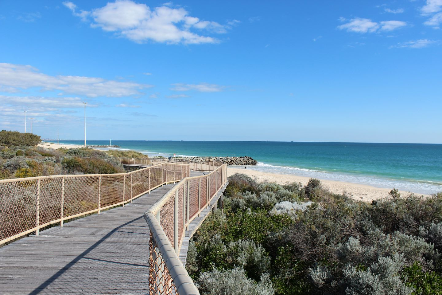 Wooden walkway between Floreat and iconic City beaches Perth Western Australia on a fine afternoon in early spring has scenic views of the Indian Ocean and dune rehabilitation.