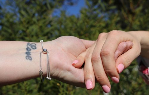 Two females holding hands, tattood wrist, nature background