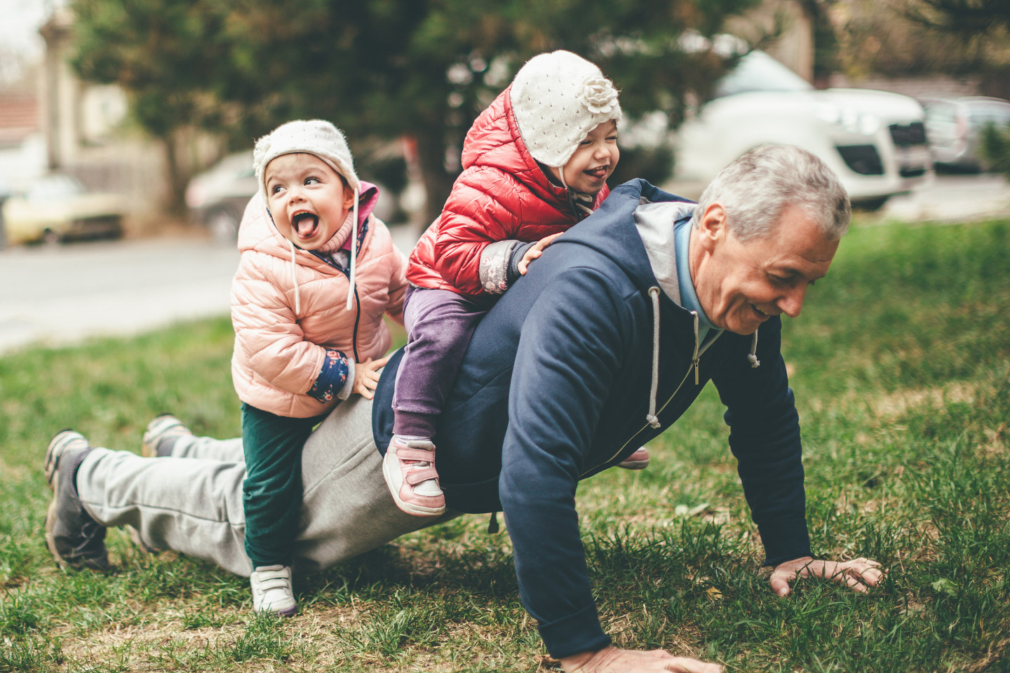 A photo of a playful grandfather and granddaughter. They are casually dressed and playing in the park. They exercise together. A grandfather is exercising while granddaughters are sitting on his back.